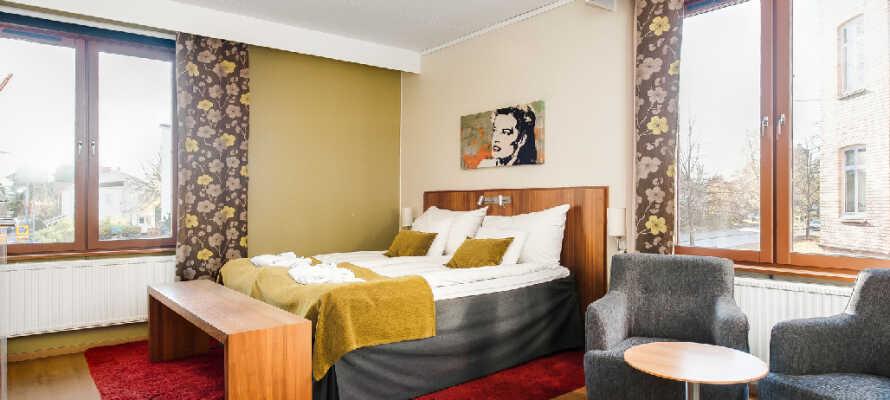 Hotellets hyggelige værelser er indrettede i lyse farver og masser af charme.